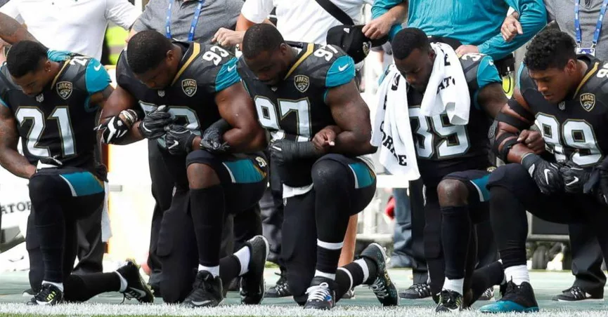 players kneeling before the football game